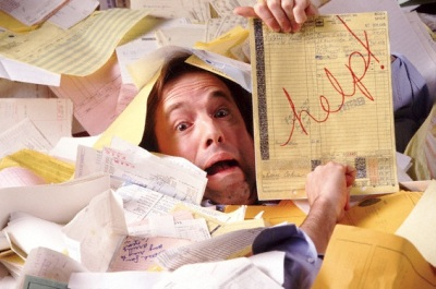 Man buried in paperwork --- Image by © Gabe Palmer/CORBIS